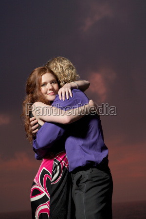 couple hugging by a beach at