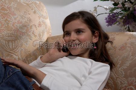 girl using mobile phone on sofa