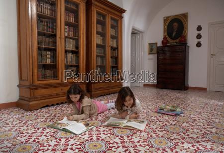 girls lying on floor reading book