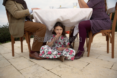 girl eating cake under table