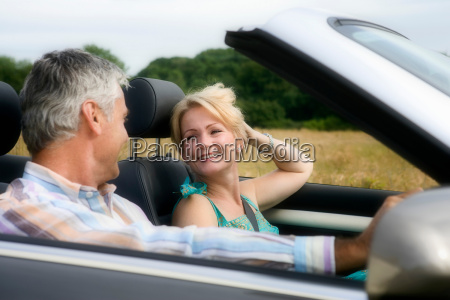 middle age couple in convertible car