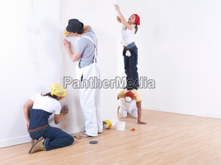 group of friends sanding wall