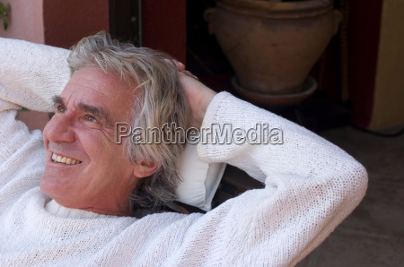 man relaxing with hands behind head