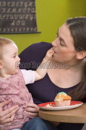young girl feeding her mother with