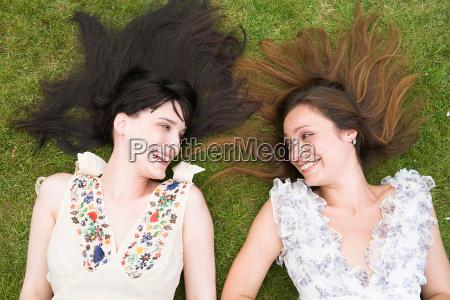 2 women laying on grass laughing