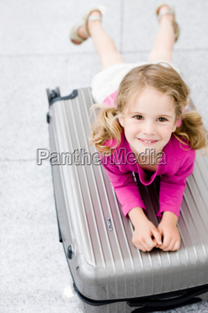 girl smiling leaning on suitcase