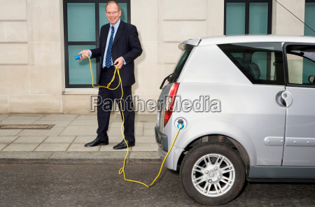 man holding cable for electric car