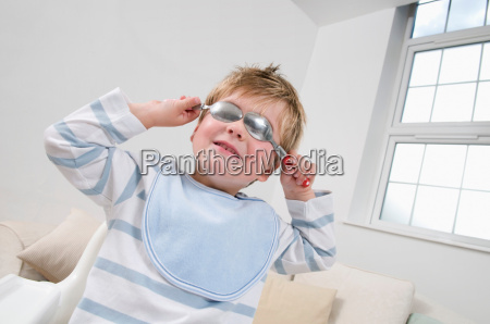 a boy holding spoons over his