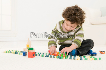 a boy playing with his toys
