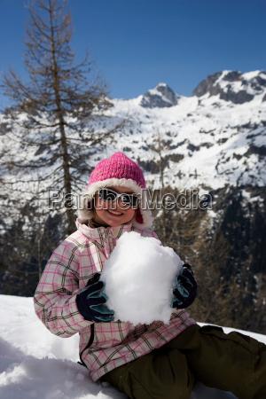 girl sitting holding snow ball