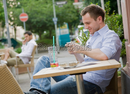 man text messaging at table