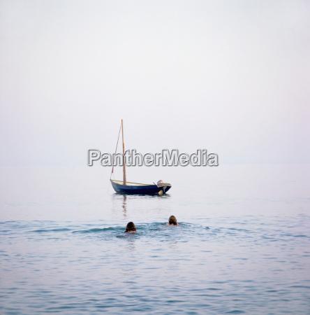 2 women swimming to boat