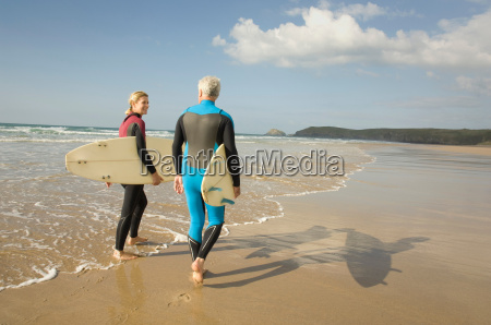 couple with surfboards on a beach