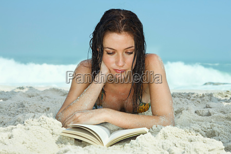 young women on beach reading a