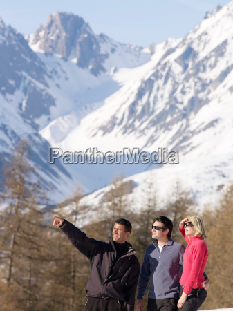 three people looking to mountain view