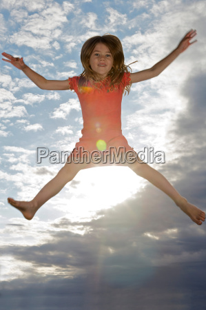 young girl jumping into the air