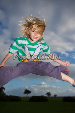 young boy jumping into the air