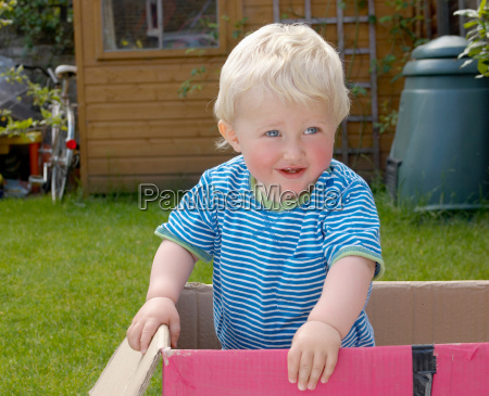 young boy standing in cardboard box