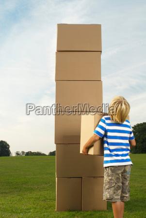 boy looking at box tower