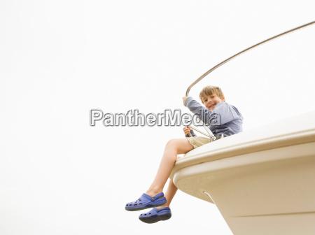 boy sitting on bow of yacht