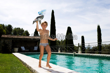boy running at swimming pool