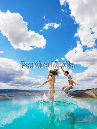 women, jumping, in, swimming, pool - 18306098