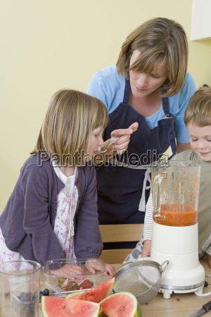 boy girl and mum making fruit