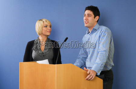 man and woman speaking from lectern