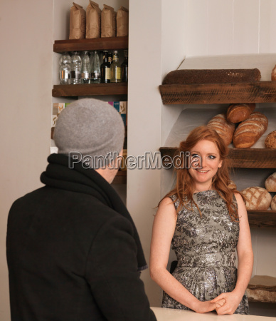 woman smiling at customer in bakery
