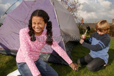 boy and girl erecting tent