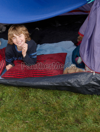 boy looking out of tent