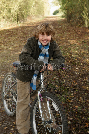 boy with bike on country lane