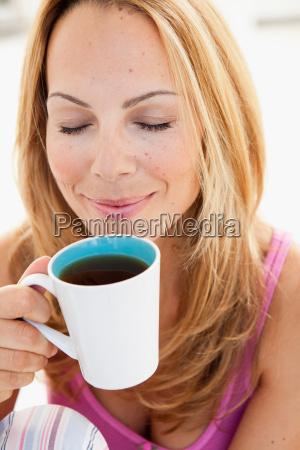 young woman enjoying cup of tea
