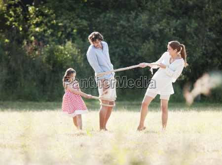 family playing with rope in field