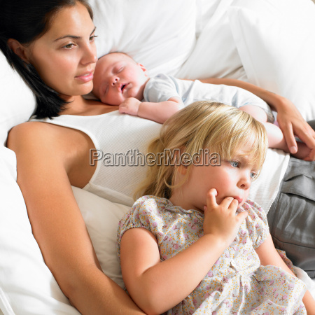 mother with babies in bed
