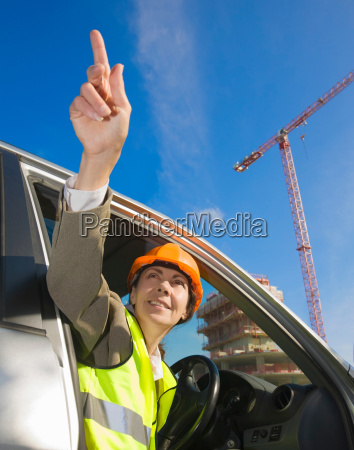woman pointing from car at building