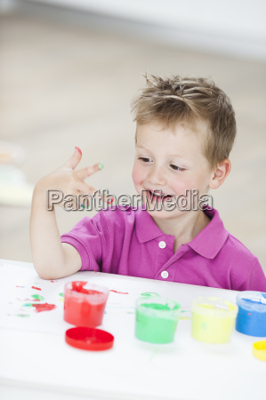 young boy playing with colours