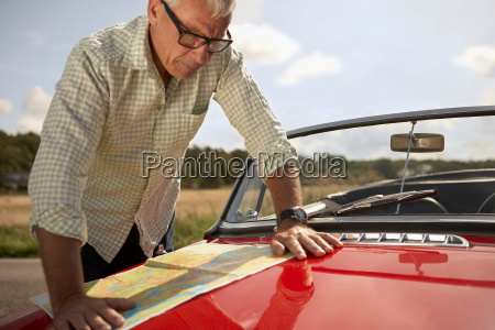 senior man with car and map