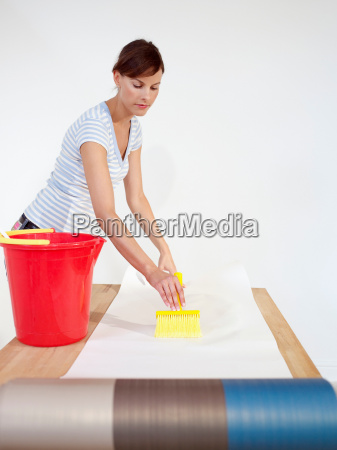 woman brushing paste onto wallpaper
