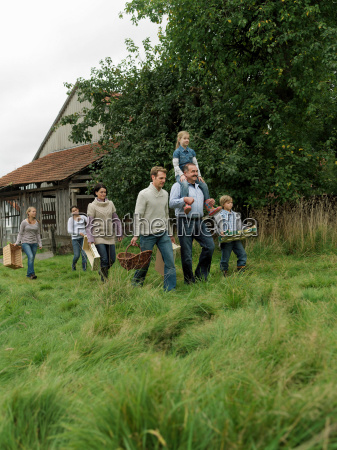 family going apple picking together