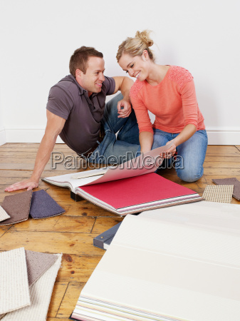couple looking through wallpaper books