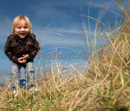 boy at beach playing with ball