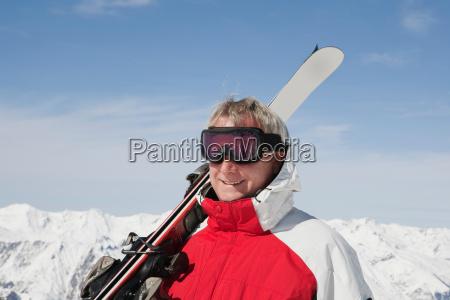 mature man holding skis