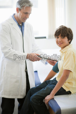 male doctor examining boy patient