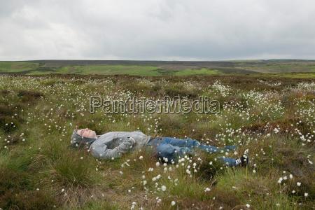 man lying in field on moors