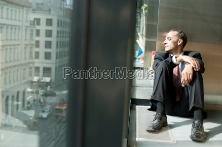 man on floor looking out a