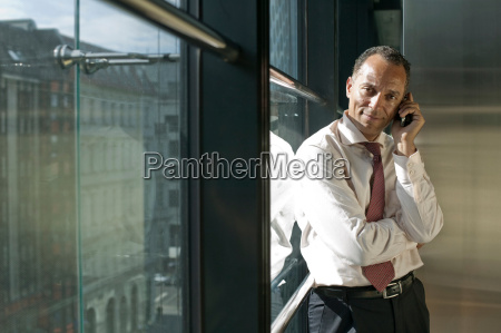 man leaning at window using cell