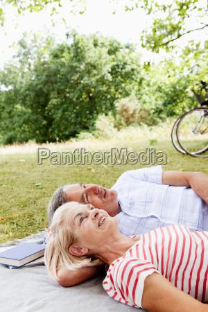mature couple cuddling on picnic blanket