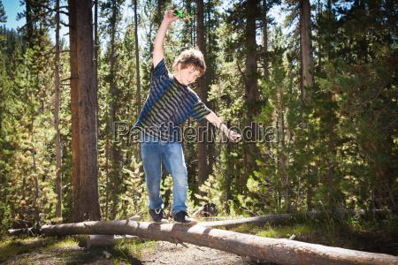 boy walking across log