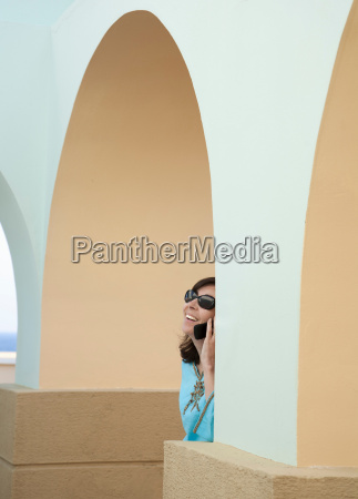 woman on phone under arches